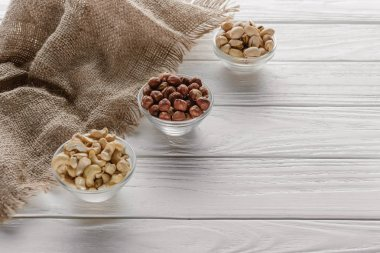 organic nuts in glass bowls on white wooden background