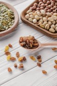 Fotografie mixed nuts in plates and raisins in spoon on white wooden table