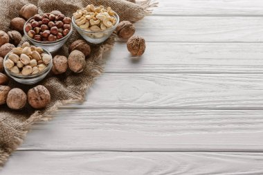 Assorted nuts in glass bowls on white wooden tabletop