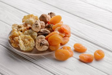 Mixed dried fruits on white plate on wooden table