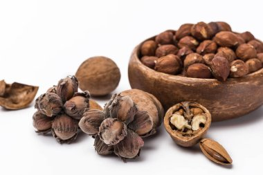hazelnuts in wooden bowl near walnuts and almond isolated on white background