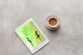 Photo top view of cup of coffee and tablet with best shopping app on screen on concrete surface