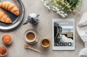 Fotografie top view of coffee with pastry and tablet with tickets app on screen on concrete surface