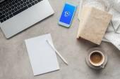 pohled shora kávy s notebookem a chytrého telefonu díky aplikaci shazam na obrazovce na betonový podklad s prázdný papír