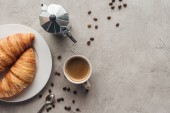 Photo top view of cup of coffee with croissants and moka pot on concrete surface with spilled coffee beans