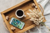 top view of cup of coffee and smartphone with ios homescreen website on screen on tray with lagurus ovatus bouquet on concrete surface