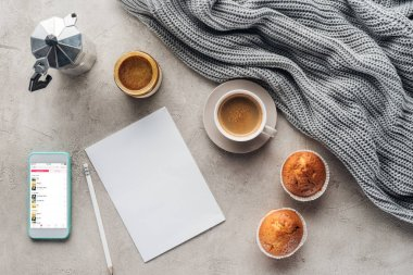 top view of cup of coffee with muffins, blank paper and smartphone with music playlist on screen on concrete surface with knitted wool drapery