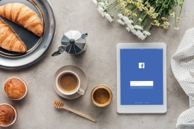 top view of coffee with pastry and tablet with facebook app on screen on concrete surface