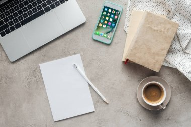 top view of coffee with laptop and smartphone with ios homescreen app on screen on concrete surface with blank paper