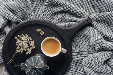 top view of cup of coffee and moka pot with field flowers on wool knitted drapery