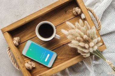 top view of cup of coffee and smartphone with twitter website on screen on tray with lagurus ovatus bouquet on concrete surface