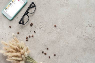 top view of smartphone with music playlist on screen with eyeglasses, spilled coffee beans and lagurus ovatus bouquet on concrete surface