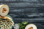 Photo top view of delicious ripe sweet melon, ice cubes, mint and melon balls on wooden surface