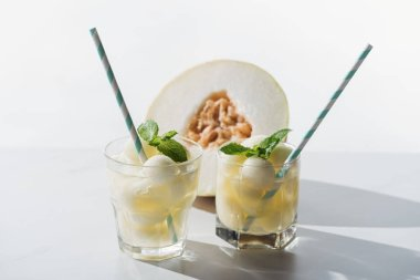 close-up view of summer drink with melon and mint in glasses and half of ripe honeydew melon on white