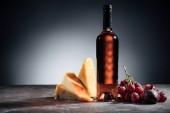 üveg vörös bor, különböző típusú ízletes sajt és a szőlő, a szürke