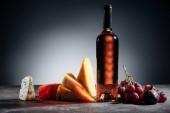 láhev červeného vína, různé typy sýrů a hrozny na grey