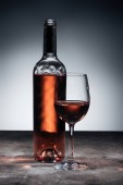 bottle of red wine and wineglass on grey