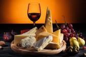 különböző típusú sajtok, pohár bor és a gyümölcsök, a narancssárga tábla