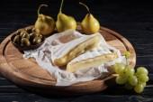 Fotografia delizioso formaggio brie, uva, pere e olive sul tagliere
