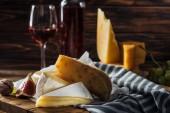 různé typy sýrů, fíky a na dřevěné desce