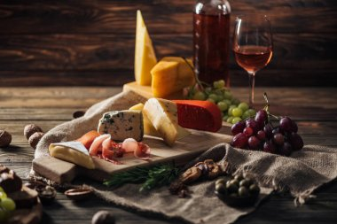 different types of cheeses, prosciutto and grapes on rustic tablecloth