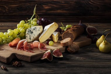 different types of cheeses, prosciutto and baguette on cutting board
