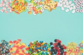 Photo top view of jelly candies, marshmallows and dragee isolated on turquoise