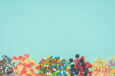 top view of different colored sweets isolated on turquoise