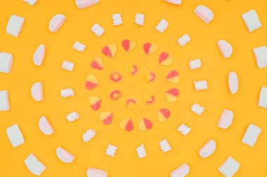top view of circles of yummy jelly candies and marshmallows isolated on orange