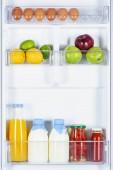 Fotografie jablka, citrony, džusy a mléko v lednici