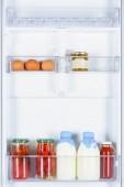 Fényképek tojás, paradicsom és üveg tejet a hűtőben
