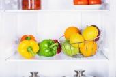 Fényképek paprika, narancs és alma a hűtőszekrény