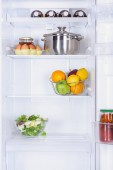 ripe fruits, salad, pan and eggs in fridge