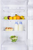 fruits, bottles of milk and salad in fridge