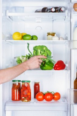 cropped image of man taking broccoli from fridge