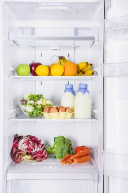 fruits, vegetables and milk with eggs in fridge