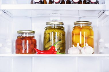 Preserved vegetables in glass jars and ripe chili peppers in fridge stock vector