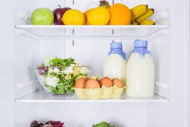 oranges, apples, eggs and milk in bottles in fridge