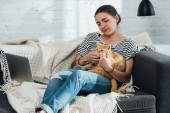 Fotografie beautiful girl sitting on sofa and palming cute red cat in living room