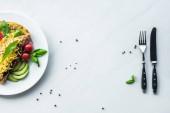 pohled shora na zdravých omeletu k snídani a příbory na bílý mramor povrch