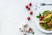 pohled shora na domácí omeleta s cherry rajčaty, kousky avokáda a příbory na bílý mramor povrch
