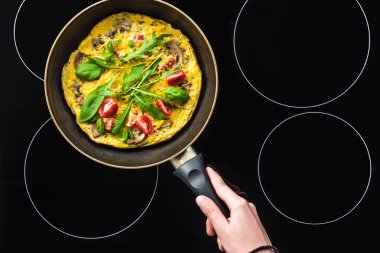 cropped shot of woman cooking omelette in frying pan on black stove