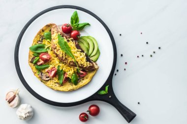 food composition with healthy omelette on wooden board on white marble tabletop