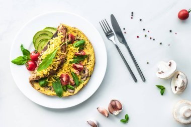 flat lay with homemade omelette with cherry tomatoes, avocado pieces, spinach and cutlery on white marble surface