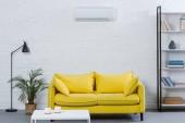 Fotografie Interieur eines modernen Wohnzimmers mit gelber Couch und Klimaanlage an weißer Wand