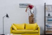 Professionelle Reparaturfirma repariert Klimaanlage, die an weißer Ziegelwand hängt