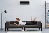 happy young woman using smartphone while lying on sofa under air conditioner hanging on wall