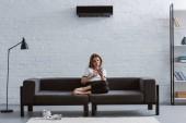 Fotografia giovane donna relaxed utilizzando smartphone sul divano sotto il condizionatore daria che appende sulla parete