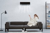 junge Frau bedeckt mit Decke auf der Couch unter der Klimaanlage an der Wand hängen und bläst gekühlte Luft