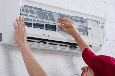 close-up shot of professional repairman changing filter for air conditioner hanging on white brick wall